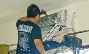 A workman cleaning and servicing a split system air conditioner.