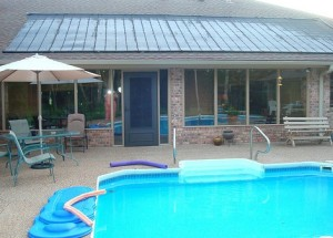 A pool area with solar collectors installed on the roof.
