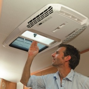 A worker installing a roof top air conditioning system in a caravan.